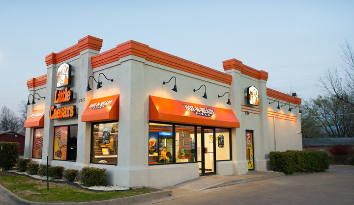 Exterior of a Little Caesars Pizza location at dusk, where Little Caesars Pizza fundraisers are sure to happen