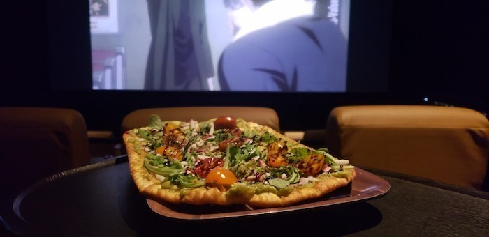 Pizza with screen in background, as seen at Studio Movie Grill fundraisers