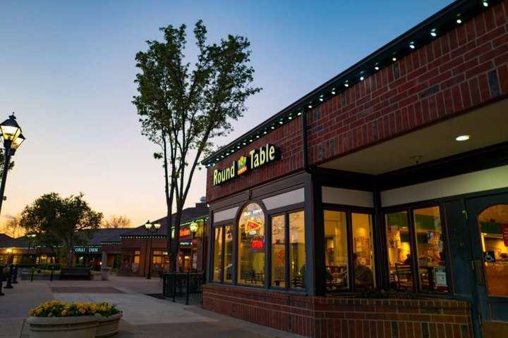 View of a Round Table Pizza location from outside at dusk, where Round Table Pizza fundraisers are sure to happen