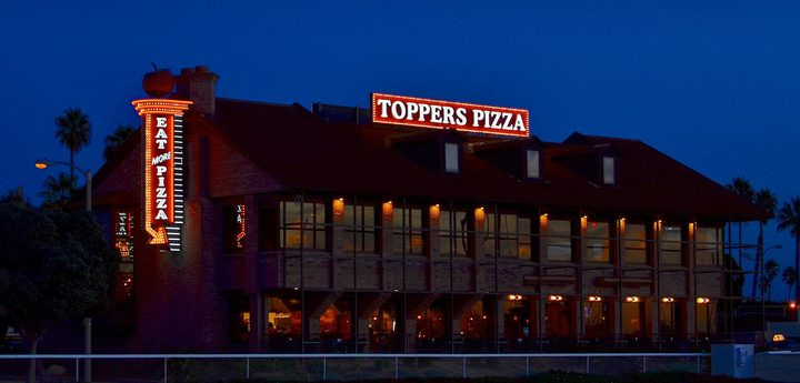 Exterior of a Toppers Pizza location in the evening, where Toppers Pizza fundraisers are sure to happen
