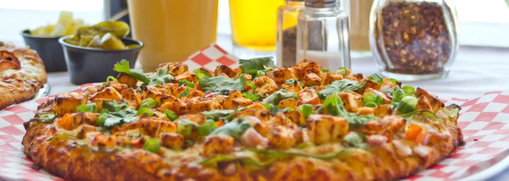 Close-up of pizza piled with fresh ingredients, as seen at Pizza House fundraisers